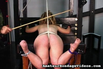 Stocks and bondages. In the stocks and with her vagina straining under a tightly pulled rope, a girl endures a beating