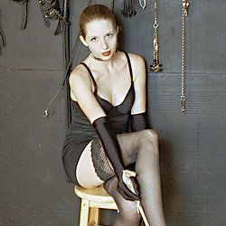 Dungeon delicacy. Redhead is surrounded by all the implements to be used in her discipline