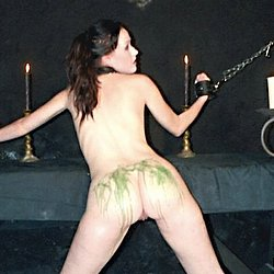 Candlewax captive. She's got wax dripped all over her--hot and colorful