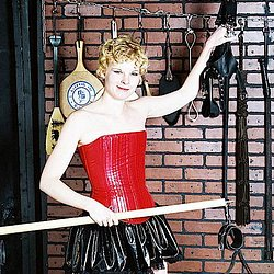 Dungeon display. Blonde in vinyl happily shows off dungeon implements