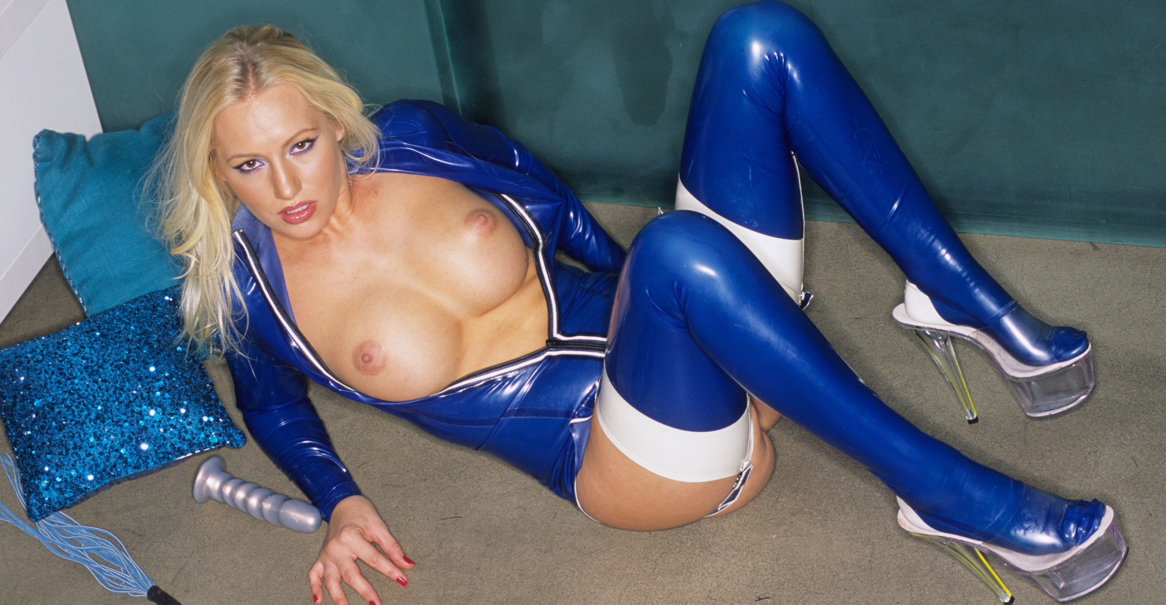 In shimmering blue. This svelte provocative babe is incased in a shinny shimmering near iridescent blue latex.  Her golden locks accent the radiance of the molded blue sumptuous body.  Two of most adorable and soft rounded breast you will ever see, explode from the glittering rubber skin.  She talks about her interest in latex and treats us to a view of her inner loveliness with some beautifully displayed open pink movements.