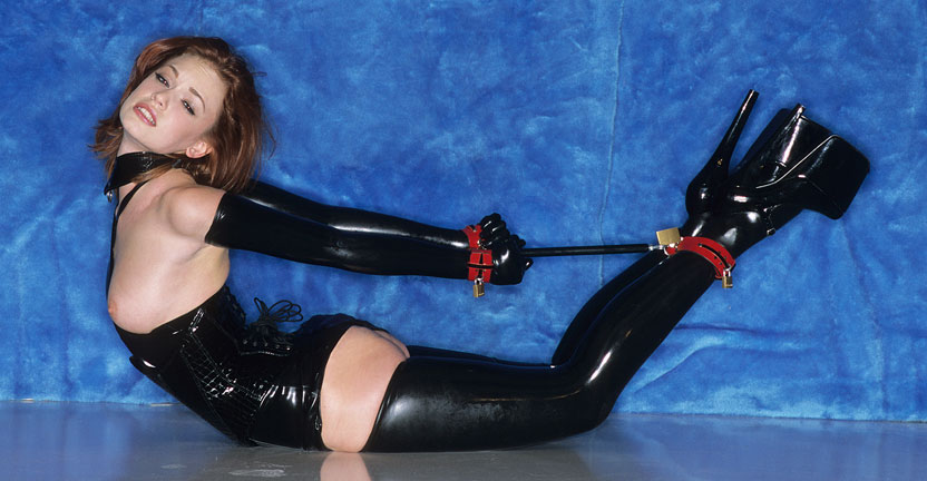 Polished and spread. This photo series features the renowned bondage model, Justine in a variety of positions.  In the first part of the series she is clad neck to foot in black latex polished to a brilliant shine.  The latex pieces are removed one a time to reveal her alabaster white anatomy in striking contrast to the latex.  She looks particularly alluring hung in one direction then the other as her lithe anatomy dangles from an overhead bar.  In another position she is hanging over a toilet bowl with clamps attached to her cunt lips and stretched wide open. There are several spread pink positions that display Justine's nether charms.  The gags embedded in her mouth add to her portrayal of absolute helplessness.