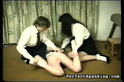 Man on girl then girl on girl. This man is wearing robes, judge-like.  Knickers don't really protect you from pain.  These girls are smokers and the spanker gives them a lesson about that.