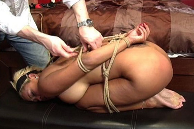 Hogtied babe blows dick. Her master has this blonde slut hogtied, her hands tied behind her back, her legs folded doubled up