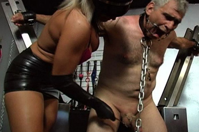 Slave on bdsm cross. He is tied up in a steel x-cross, which allows him to sit if his dominatrix allowed him to